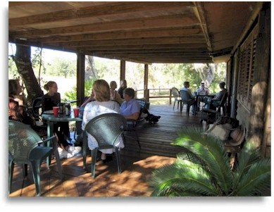 Group sharing a meal on the porch at Rasayana Cove Ayurvedic Retreat